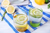 foto of cucumber  - Fresh water with lemon and cucumber in glassware on wooden table - JPG