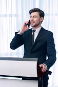 stock photo of motivation talk  - Business manager standing at the tribune in meeting room talks over the phone smiling - JPG