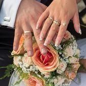stock photo of wedding feast  - Wedding bouquet hands of bride and groom - JPG