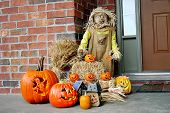 stock photo of jack-o-laterns-jack-o-latern  - Holloween scene with Pumpkins and scarecrow on porch - JPG