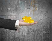 stock photo of jigsaw  - Hand showing gold jigsaw puzzle piece with business concept doodles wall background - JPG