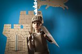 stock photo of berserk  - scared child knight is looking from the shield - JPG