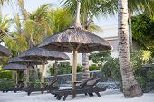 stock photo of mauritius  - Deck chairs under an umbrella on a tropical beach. Shooting on the island of Mauritius Indian Ocean. - JPG