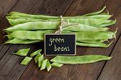 image of phaseolus  - Piattoni green beans with small chalkboard on the old wooden table - JPG