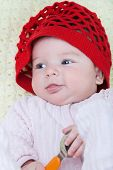 pic of knitted cap  - Baby girl in a red cap hand knitted with a spoon in his hand - JPG