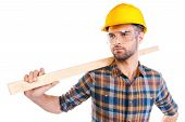 pic of protective eyewear  - Confident young male carpenter in hardhat and protective eyewear carrying wooden balk on shoulder while standing against white background - JPG