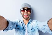 stock photo of top-hat  - Top view of handsome young man in hat and glasses making selfie and smiling while standing against grey background - JPG