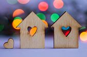 image of two hearts  - Two wooden houses with hole in the form of heart with little heart on colorful bokeh background - JPG