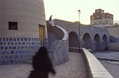 pic of burqa  - Sana capital city of Yemen in morning with woman and man walking towards the old part - JPG