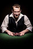 stock photo of gambler  - A male gambler feels fortunate and goes all inn - JPG