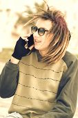 image of rasta  - portrait of young guy outdoor with rasta hair smiling with smartphone in a lifestyle concept with a warm filter applied - JPG