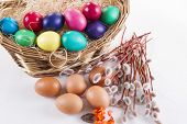 foto of willow  - Wicker basket with colored eggs and willow branches on a white background - JPG