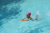 foto of swimming  - Little Young Girl Swimming in Blue Water of a Swimming Pool - JPG