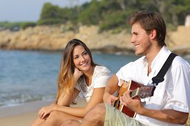 stock photo of flirt  - Man flirting playing guitar while a girl looks him amazed with the sea in the background - JPG