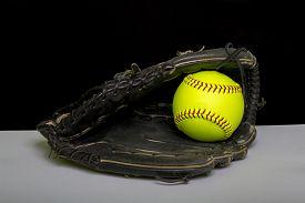 stock photo of softball  - A black fastpitch softball mitt with a yellow fastpitch softball in the webbing - JPG