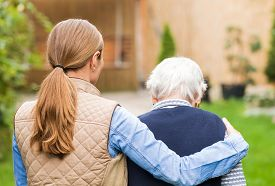 stock photo of retirement age  - Young carer walking with the elderly woman in the park - JPG