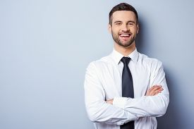 pic of candid  - Portrait of handsome young man in shirt and tie keeping arms crossed and smiling while standing against grey background - JPG