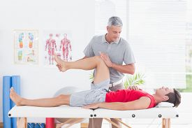 foto of physiotherapist  - Physiotherapist doing leg massage to his patient in medical office - JPG