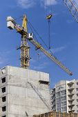 image of construction crane  - Construction crane against the blue sky and building under construction - JPG