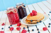 picture of picking tray  - Stack of wheat golden pancakes or pancake cake with freshly picked raspberries on a dessert plate - JPG