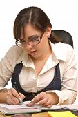 Young Businesswoman In Glasses Writing
