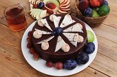 foto of hot-chocolate  - whole big chocolate cream brownie cake topped with white chocolate and cream flowers with hot tea cup decorated with fruits apple plum and grape on plate on wooden table - JPG