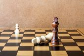 image of chessboard  - One chess king dominating another on the chessboard - JPG