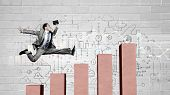 stock photo of step-up  - Young businessman stepping up on chart bar - JPG