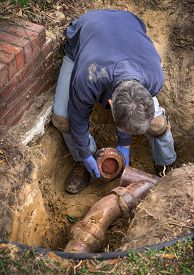 foto of pipe-welding  - Man removing sections of old clogged clay ceramic sewer pipe in trench in the ground - JPG