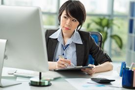pic of employee  - Young employee working at her pc at office - JPG