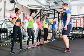 Men and women with coach at kettlebell functional training in fitness center poster