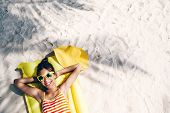 Child girl in yellow swimwear and sunglasses chilling on lilo under palm tree on sand at the beach.  poster