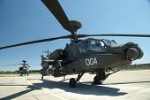 stock photo of longbow  - A pair of helicopters sit on the helipad on a sunny day - JPG
