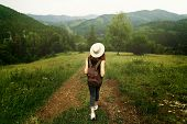 Woman Traveler With Backpack And  Hat Walking In Amazing Mountains And Forest, Wanderlust Travel Con poster