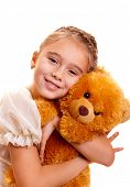 A cute little girl embracing teddy bear