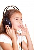 Cute little girl listening music in headphones