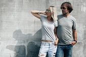 Two hipster models man and woman wearing blank gray t-shirt, jeans and sunglasses posing against rou poster