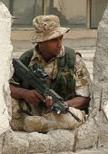 British Soldier Against A Damaged Building In Iraq.