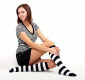 Sexy girl in funny socks posing on her knees. Studio shot over light background