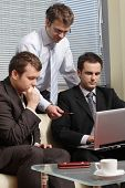 Three business men working together on laptop in the office. one is standing two are sitting on leat