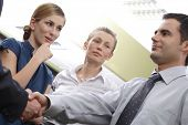 Male business employee shaking the hand of an unseen male employee, while two female employees, one with great interest, look on.  In an office setting.
