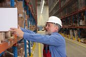 older worker in uniform putting heavy box on  shelf in warehouse