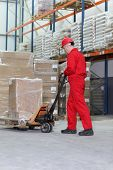 worker in red uniform at work  with hand powered pallet jack in warehouse