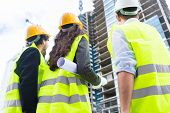 Construction engineers or architects at building site of highrise building poster