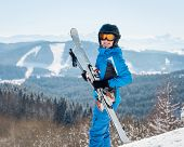 Happy Female Skier Smiling To The Camera, Holding Her Skis, Wearing Blue Ski Suit And Black Helmet A poster