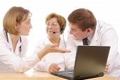 picture of medical staff  - Two young interns consulting medical problem with senior doctor wearing headset sitting behind desk with laptop over white - JPG