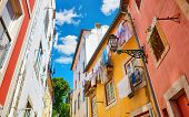 Lisbon, Portugal. Antique Alfama district with coloured houses on background of blue sky with clouds poster