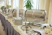 stock photo of wedding feast  - Buffet Table with dishware waiting for guests - JPG