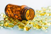Omega 3 gel capsules. Fish oil pills. Healthy omega-3 in glass bottle. poster