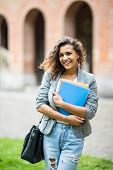 Young Caucasian College Student With Book In College Campus. University Student Going To College. poster